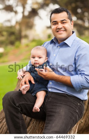 Handsome Hispanic Father and Son Posing for A Portrait in the Park. - stock photo