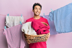Handsome hispanic man doing laundry holding wicker basket smiling looking to the side and staring away thinking.