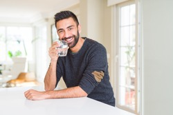 Handsome hispanic man drinking a fresh glass of water with a happy face standing and smiling with a confident smile showing teeth