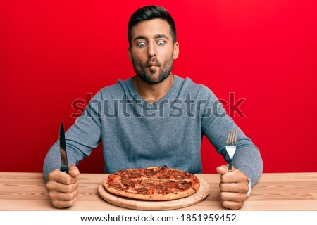 Handsome hispanic man eating tasty pepperoni pizza making fish face with mouth and squinting eyes, crazy and comical.  Stockfoto ©