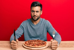 Handsome hispanic man eating tasty pepperoni pizza skeptic and nervous, frowning upset because of problem. negative person.