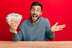 Handsome hispanic man holding bunch of 50 euro banknotes celebrating achievement with happy smile and winner expression with raised hand