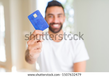 Handsome hispanic man holding credit card with a happy face standing and smiling with a confident smile showing teeth
