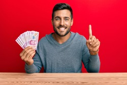 Handsome hispanic man holding mexican pesos smiling with an idea or question pointing finger with happy face, number one