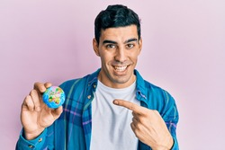Handsome hispanic man holding small world ball smiling happy pointing with hand and finger
