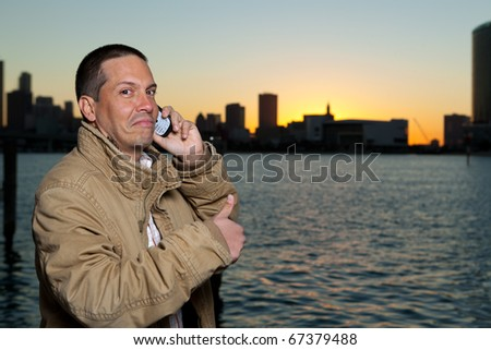 Handsome hispanic man in an urban lifestyle pose talking on a mobile phone with a downtown skyline in the background in the late afternoon at sunset.