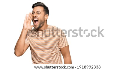 Handsome hispanic man wearing casual clothes shouting and screaming loud to side with hand on mouth. communication concept.  Foto stock ©