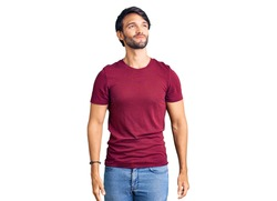 Handsome hispanic man wearing casual clothes smiling looking to the side and staring away thinking.