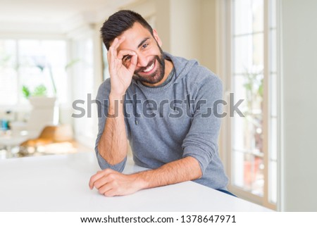 Handsome hispanic man wearing casual sweatshirt at home doing ok gesture with hand smiling, eye looking through fingers with happy face.
