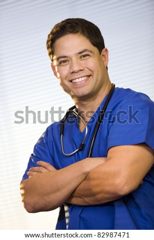 Handsome Hispanic man wearing scrubs and stethoscope.