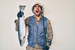 Handsome hispanic man with beard holding fishing rod and raw salmon angry and mad screaming frustrated and furious, shouting with anger looking up.