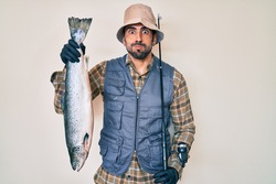Handsome hispanic man with beard holding fishing rod and raw salmon puffing cheeks with funny face. mouth inflated with air, catching air.