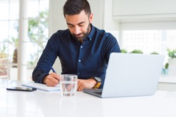 Handsome hispanic man working using computer and writing on a paper with a confident expression on smart face thinking serious
