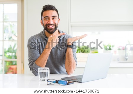 Handsome hispanic man working using computer laptop amazed and smiling to the camera while presenting with hand and pointing with finger.
