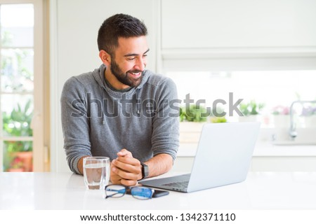 Handsome hispanic man working using computer laptop looking away to side with smile on face, natural expression. Laughing confident.
