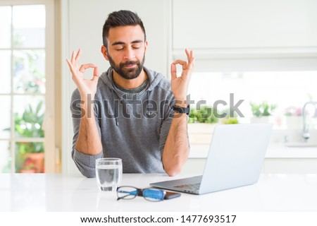 Handsome hispanic man working using computer laptop relax and smiling with eyes closed doing meditation gesture with fingers. Yoga concept.