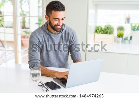 Handsome hispanic man working using computer laptop with a happy face standing and smiling with a confident smile showing teeth