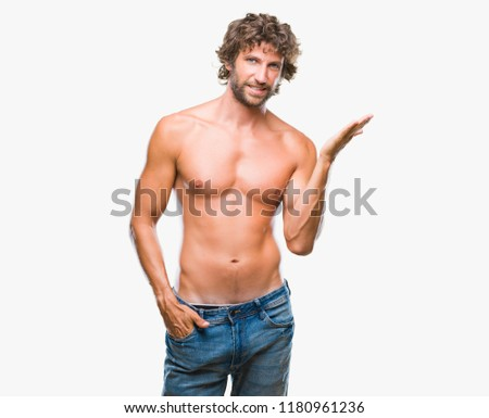 Handsome hispanic model man sexy and shirtless over isolated background smiling cheerful presenting and pointing with palm of hand looking at the camera.