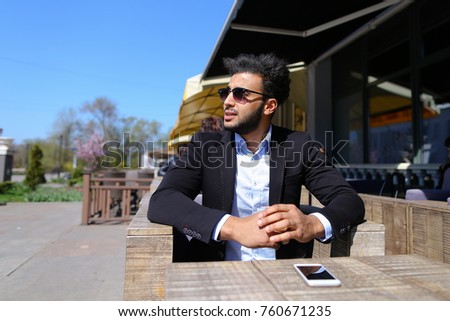 Handsome human clicking on phone s screen and laughing. Attractive guy has short dark hair, beard, dimple on cheek and wears sunglasses. Concept of modern technologies wifi new apps and fiction on #760671235