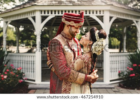 Handsome Indian groom in red hat holds in his hands a gorgeous bride