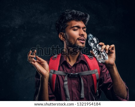 Handsome Indian hiker with backpack exhausted by heat gladly drinks refreshing water. Studio photo against a dark textured wall