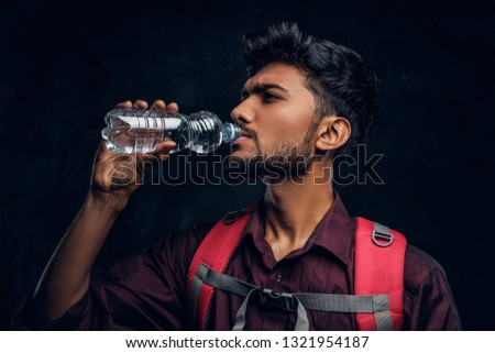 Handsome Indian hiker with backpack exhausted with thirst drinking water. Studio photo against a dark textured wall