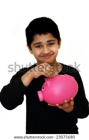 Handsome Indian kid saving money in a piggy bank