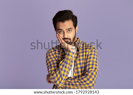 Handsome Indian man feeling bored or tired over lilac background Stock photo ©