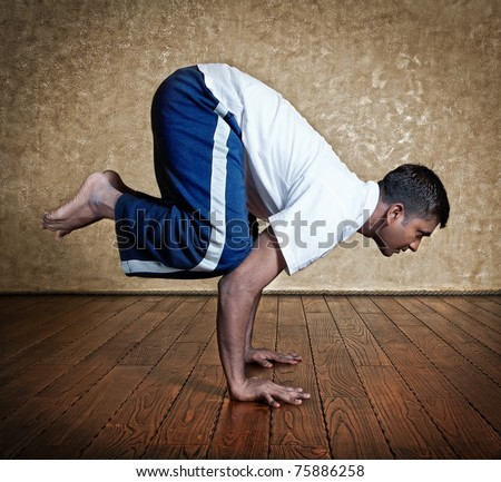 handsome indian man in white shirt doing bakasana crane