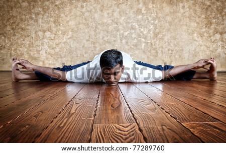 Handsome Indian man in white shirt doing Upavista Konasana seated angle pose indoors on wooden floor at grunge background - stock photo