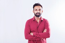 Handsome Indian man looking at camera over white studio background