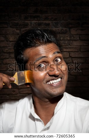 Handsome Indian man painting his face by paint brush close-up at brick wall background