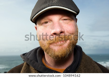 Handsome Irish Man with a red beard wearing a duckbill cap