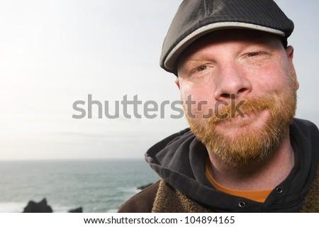Handsome Irish Man with a red beard wearing a duckbill cap - stock photo
