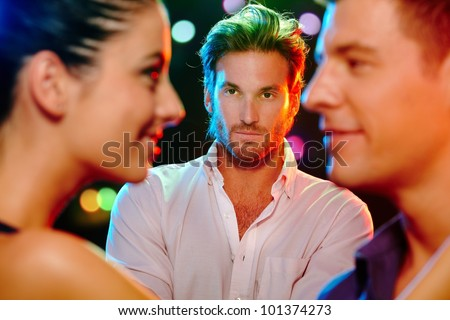 Handsome jealous man looking at flirting couple on dance floor.