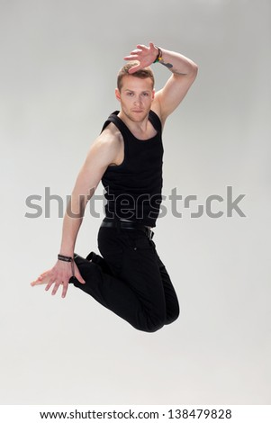 Handsome jumping guy in black clothes