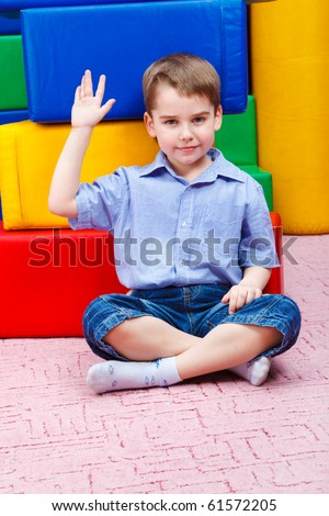 Handsome kid sitting in front of large colorful blocks
