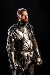 handsome knight in armor looking away isolated on black