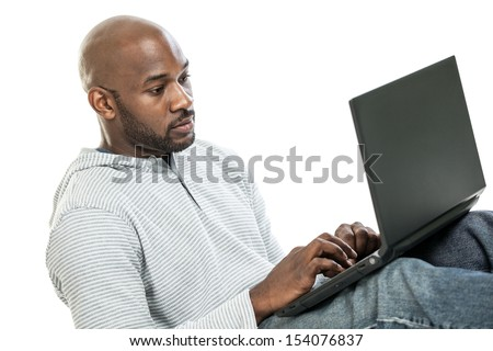 Handsome late 20s black man typing on the computer isolated on a white background