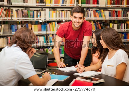 Handsome Latin man helping his colleagues out by explaining some of his work at the library
