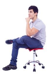 Handsome latin man sitting on a chair, isolated over a white background