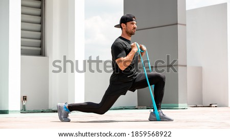 Handsome Latino sports man doing lunge workout with resitance band outdoors in the sun
