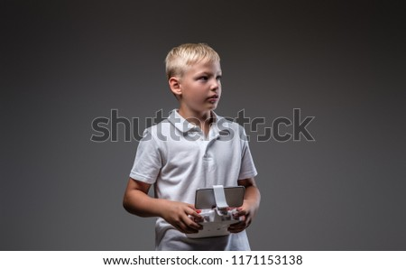 Handsome little boy boxer with blonde hair dressed in a white t-shirt holds a quadcopter control remote.