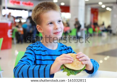 handsome little boy eating burger