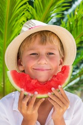 Handsome little boy eating slice of red ripe watermelon. Holidays and vacations, travel concept. Palm leaves, sunny summer day, summertime.