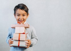 Handsome little boy holding a lot of handmade gift boxes. Portrait of stylish little boy holding real box on gray background. Get your holiday bonus concept. banner
