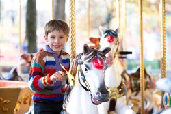 Handsome little boy is riding a carousel. A child on a horse carousel.
