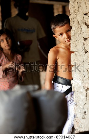 handsome little boy leaning against the wall, Indian boy from a poor family without a shirt
