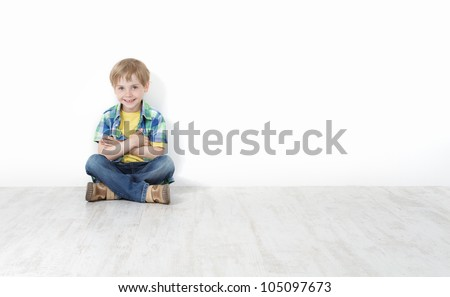 Handsome little boy sitting on floor leaning against white wall. Legs and hands crossed.