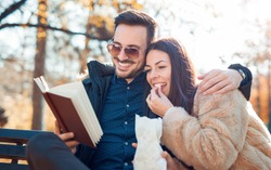 Handsome loving couple sitting in the autumn park, reading a book and eating popcorn. Love and tenderness. Relationships, friendships, education, lifestyle concept